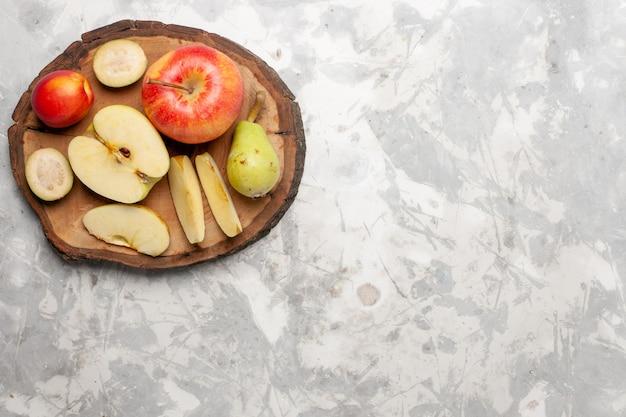 Vista superior de maçãs frescas com peras frescas em um espaço em branco claro