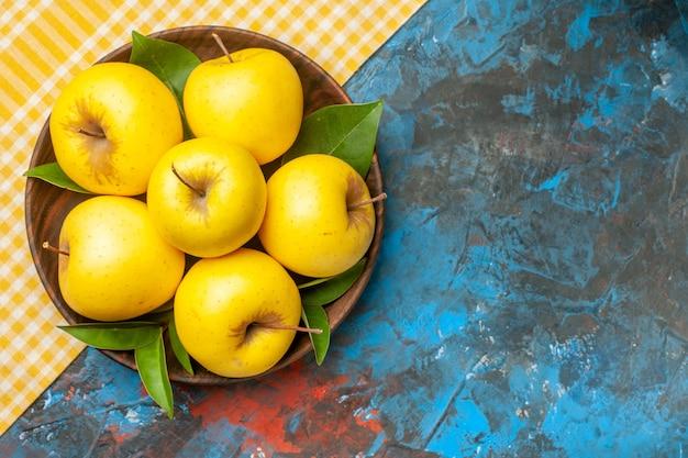 Vista superior de maçãs frescas doces dentro do prato sobre fundo azul