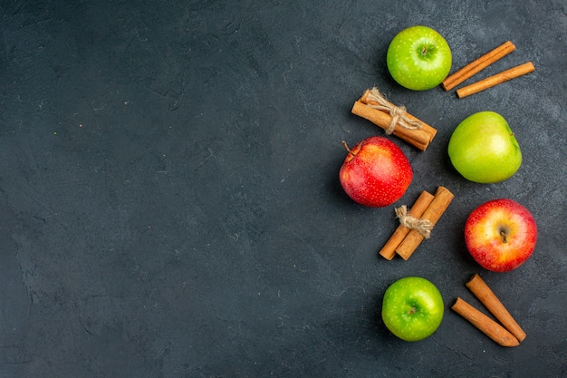 Vista superior de maçãs frescas em bastões de canela na superfície escura do espaço livre