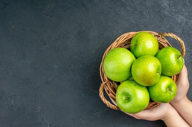 Vista superior de maçãs frescas em uma cesta de vime em uma mão feminina no espaço livre de superfície escura