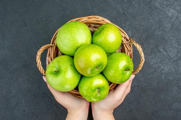 Vista superior de maçãs frescas em uma cesta de vime na mão feminina na superfície escura
