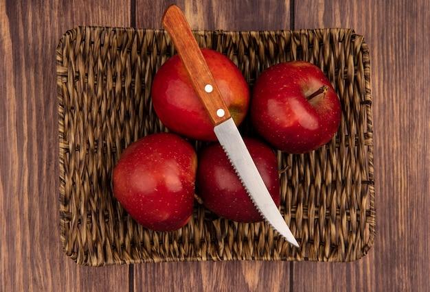 Vista superior de maçãs frescas, suculentas e vermelhas em uma bandeja de vime com uma faca em um fundo de madeira