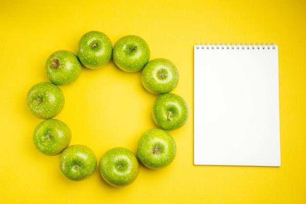 Vista superior de maçãs maçãs verdes ao lado do caderno branco