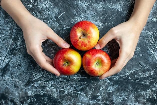 Vista superior de maçãs maduras em mãos femininas em fundo cinza com local de cópia