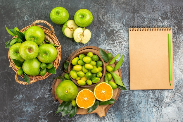 Vista superior de maçãs no tabuleiro com cesta de frutas cítricas e lápis de maçã