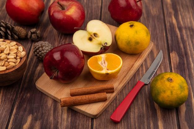 Vista superior de maçãs orgânicas em uma placa de cozinha de madeira com meias tangerinas e paus de canela com faca com amendoim em uma tigela de madeira com maçãs isoladas em um fundo de madeira