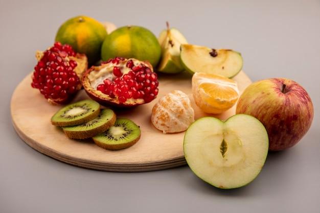 Vista superior de maçãs saudáveis com frutas como tangerinas de romã e kiwi em uma placa de cozinha de madeira