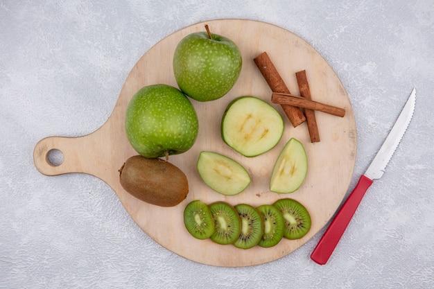 Vista superior de maçãs verdes com fatias de kiwi e canela em um suporte com uma faca em um fundo branco