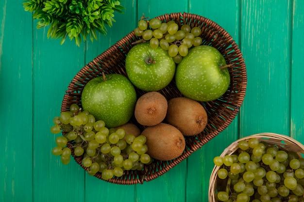 Vista superior de maçãs verdes com kiwi e uvas em cestas sobre fundo verde