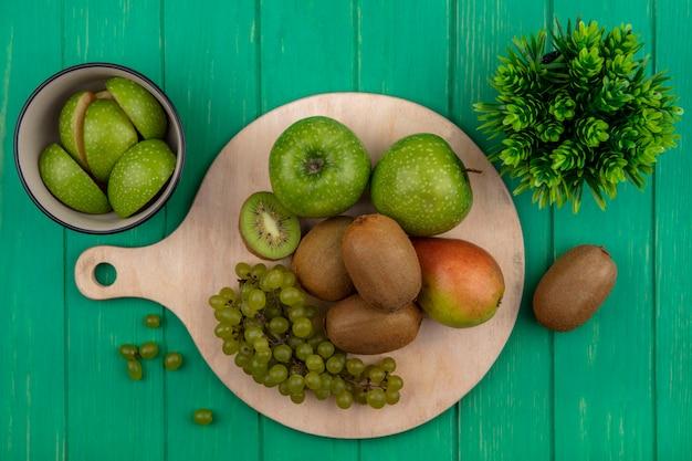 Vista superior de maçãs verdes com uvas verdes kiwi e pêra em um suporte sobre um fundo verde
