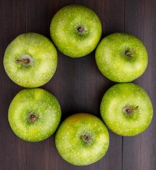 Vista superior de maçãs verdes e frescas, dispostas em forma de círculo em uma superfície de madeira