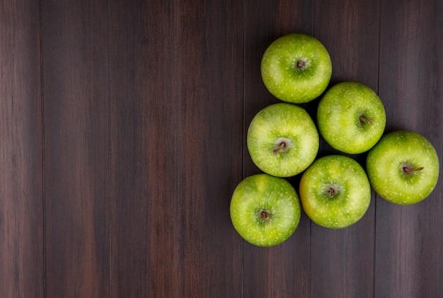 Vista superior de maçãs verdes e frescas, dispostas em forma de pirâmide em uma superfície de madeira