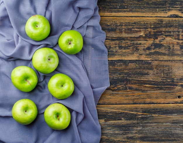 Vista superior de maçãs verdes em fundo de madeira e têxtil