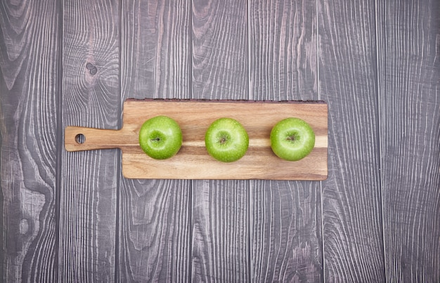 Vista superior de maçãs verdes em uma placa de madeira