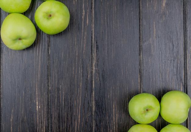 Vista superior de maçãs verdes nos lados em fundo de madeira com espaço de cópia
