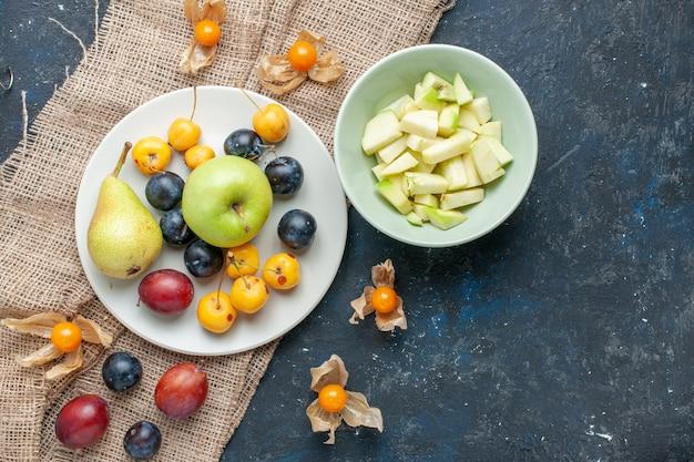 Vista superior de maçãs verdes suaves e suculentas com maçã fatiada dentro do prato com outras frutas na mesa azul escura, vitamina de saúde de frutas frescas