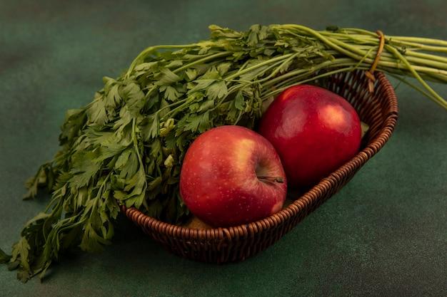Vista superior de maçãs vermelhas e doces frescas e salsa em um balde em um fundo verde