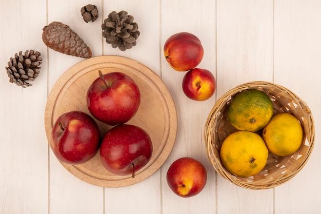 Vista superior de maçãs vermelhas em uma placa de cozinha de madeira com tangerinas em um balde com pêssegos e pinhas isoladas em uma superfície de madeira branca