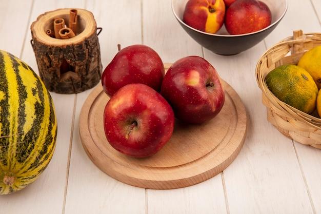 Vista superior de maçãs vermelhas frescas em uma placa de cozinha de madeira com melão melão com tangerinas em um balde em um fundo branco de madeira