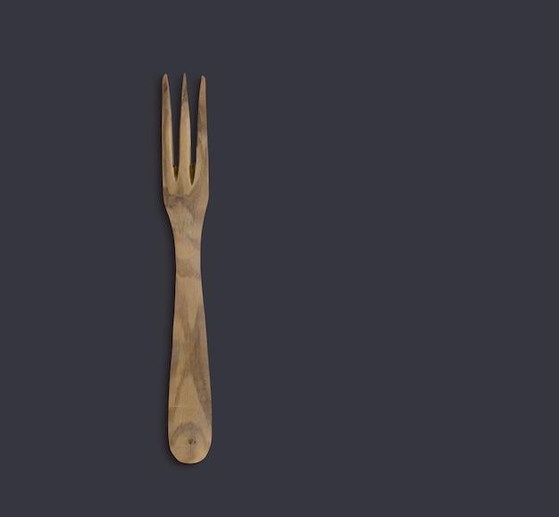 Vista superior de madeira verde-oliva cozinheiro serve garfo isolado no preto