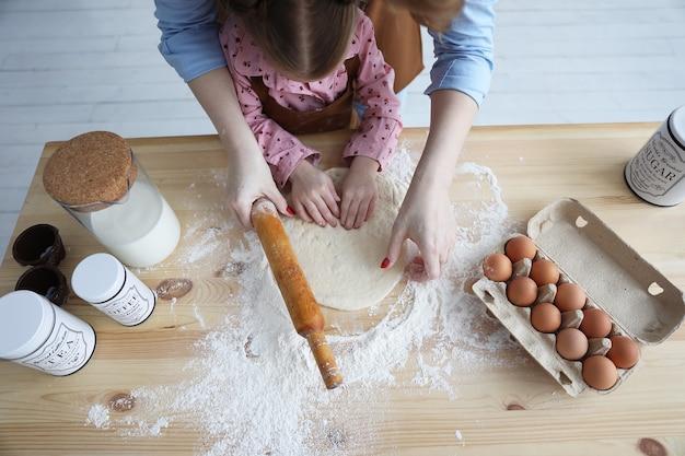Vista superior de mãe e filha na cozinha cozinhando com farinha e ovos