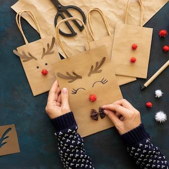 Vista superior de mãos decorando sacolas de papel de natal com uma linda rena