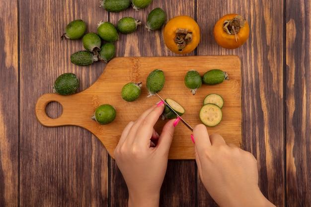 Vista superior de mãos femininas cortando feijoa em uma tábua de cozinha de madeira com uma faca com frutas frescas de caqui e feijoas isoladas em uma parede de madeira