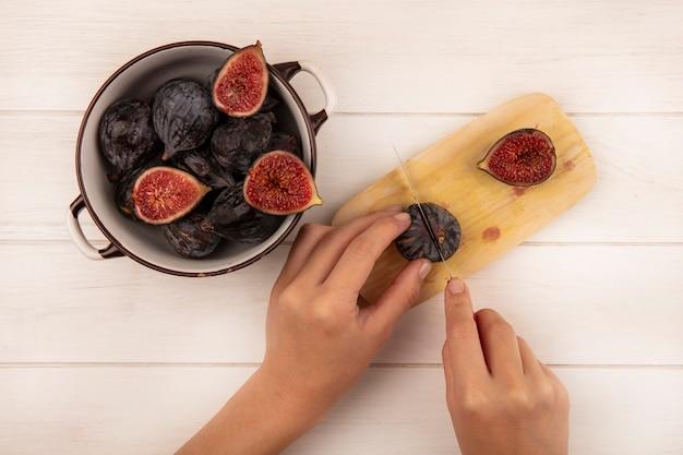 Vista superior de mãos femininas cortando figos pretos doces frescos em uma placa de cozinha de madeira com uma faca em uma parede de madeira branca