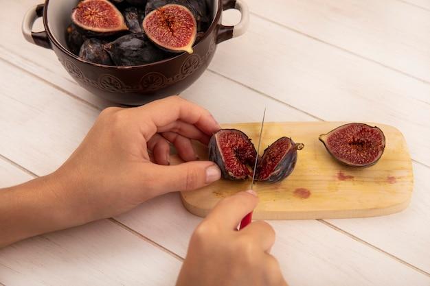 Vista superior de mãos femininas cortando figos pretos em uma placa de cozinha de madeira com uma faca em uma parede de madeira branca