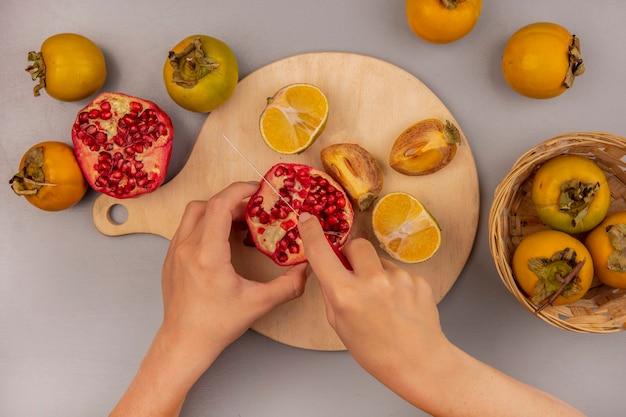 Vista superior de mãos femininas cortando frutas de romã em uma placa de cozinha de madeira com uma faca