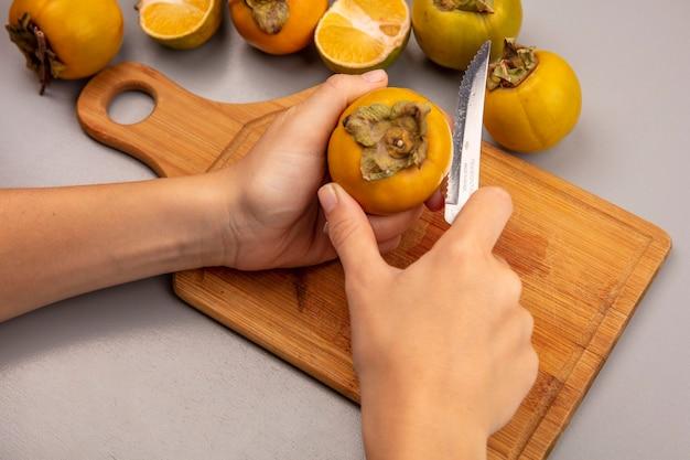 Vista superior de mãos femininas cortando frutas frescas de caqui em uma placa de cozinha de madeira com uma faca