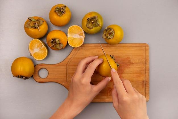 Vista superior de mãos femininas cortando frutos de caqui em uma placa de madeira da cozinha com uma faca