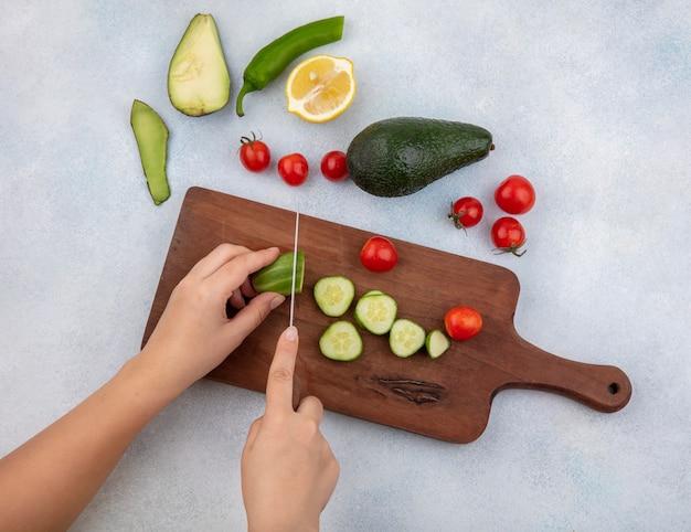 Vista superior de mãos femininas cortando pepino em fatias na mesa da cozinha com uma faca com tomate cereja e abacate e limão isolado no branco