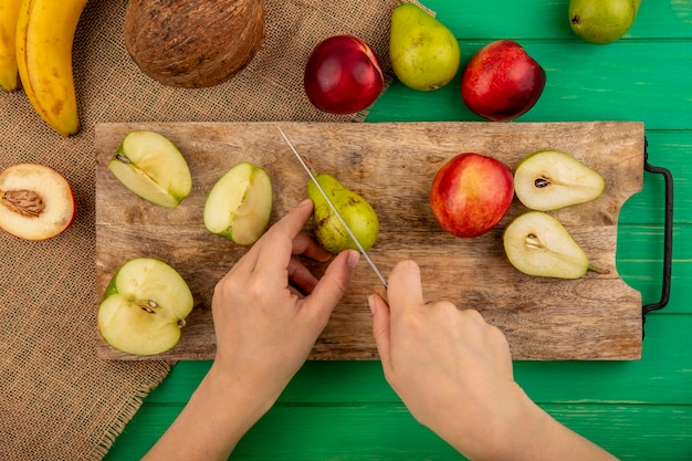 Vista superior de mãos femininas cortando pêra com faca e pêra meio cortada e pêssego inteiro na tábua com banana de coco em pano de saco e fundo verde