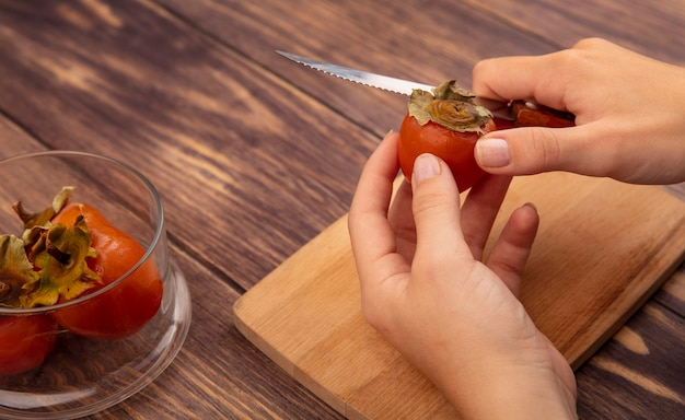 Vista superior de mãos femininas cortando um caqui fresco e macio em uma placa de cozinha de madeira com uma faca em uma superfície de madeira