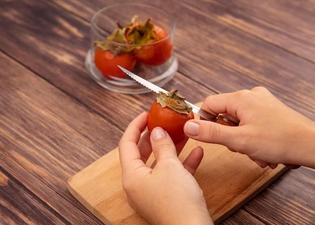 Vista superior de mãos femininas cortando um caqui fresco em uma placa de cozinha de madeira com uma faca em uma superfície de madeira