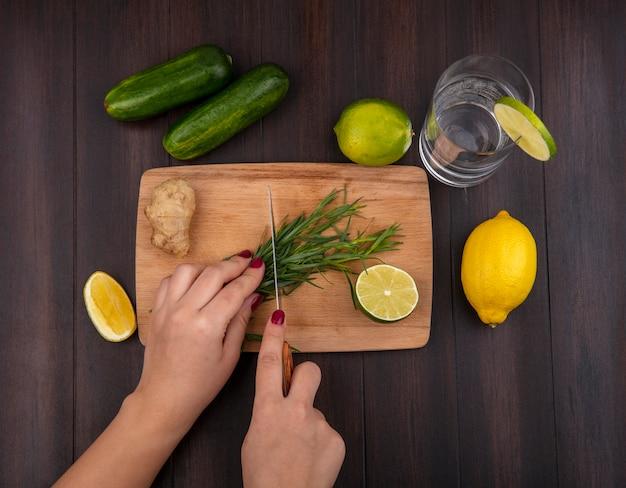 Vista superior de mãos femininas cortando verduras de estragão na mesa de madeira da cozinha com uma faca com limões na madeira