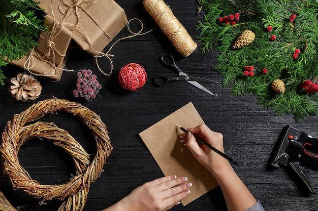 Vista superior de mãos femininas embrulhar presentes de ano novo embalados e pergaminhos ramos de abeto e ferramentas em ...
