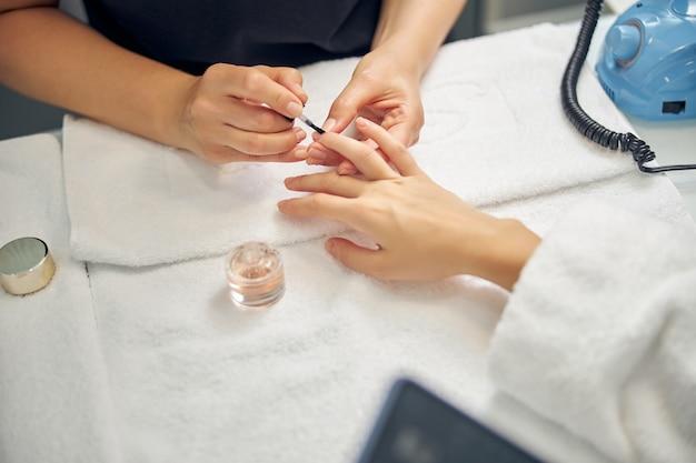 Vista superior de mãos femininas enquanto o mestre está aplicando as unhas no salão