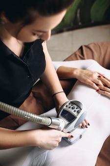 Vista superior de mãos femininas fazendo terapia anti-idade com glp para remover a celulite em um corpo feminino.
