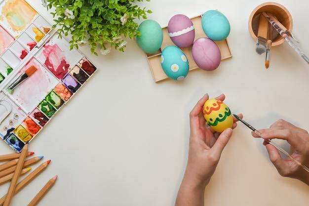 Vista superior de mãos femininas pintando ovos para se preparar para o festival de páscoa na mesa de artesanato com ferramentas de pintura