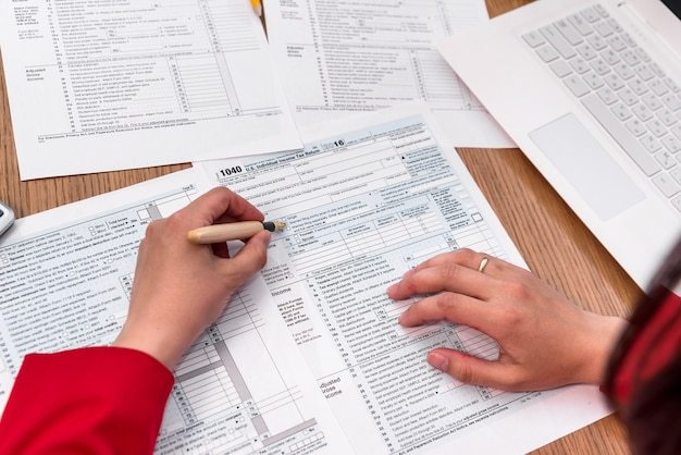 Vista superior de mãos femininas preenchendo formulário fiscal 1.040