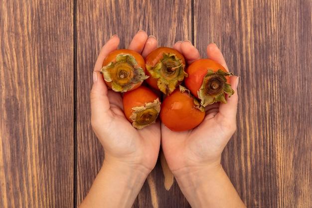 Vista superior de mãos femininas segurando caquis frescos macios e suculentos em uma superfície de madeira