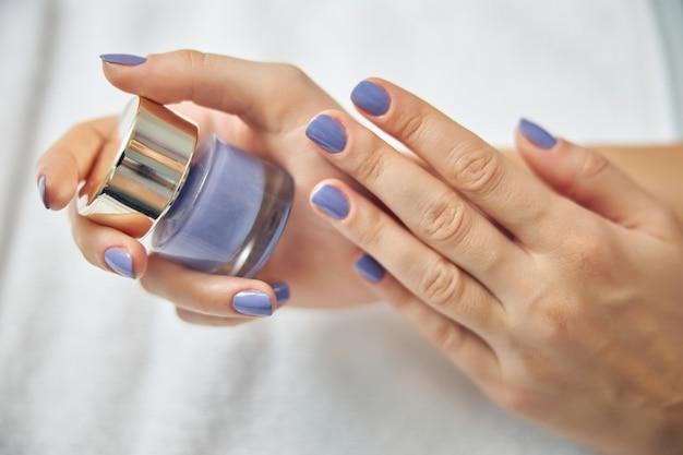 Vista superior de mãos femininas segurando cosméticos para unhas depois de fazer as unhas coloridas