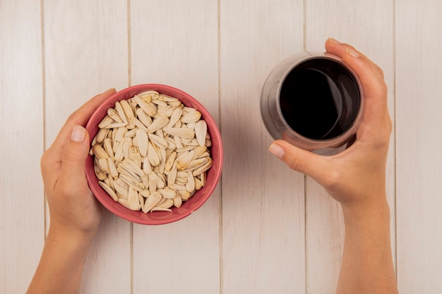 Vista superior de mãos femininas segurando em uma mão uma tigela de sementes de girassol brancas e na outra um copo de coca-cola em uma mesa de madeira bege