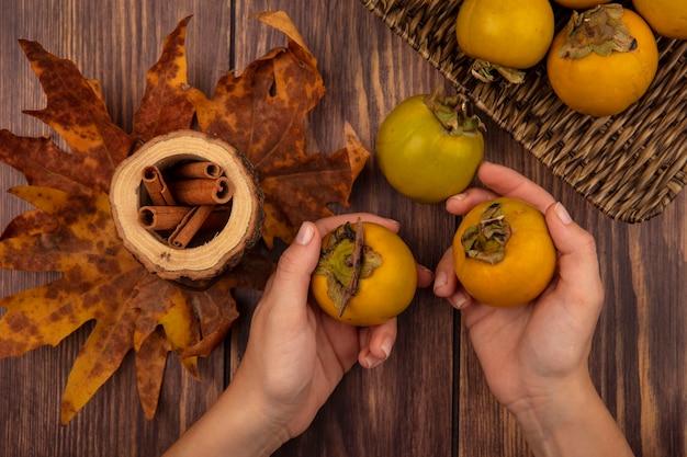 Vista superior de mãos femininas segurando frutas de caqui com paus de canela em uma jarra de madeira com folhas em uma mesa de madeira