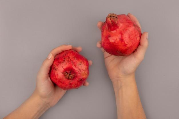 Vista superior de mãos femininas segurando romãs vermelhas frescas