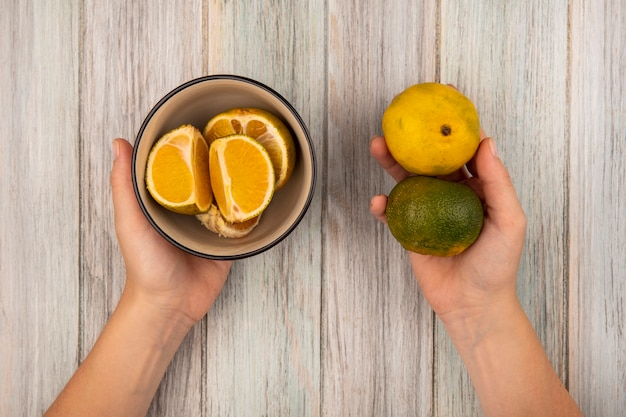 Vista superior de mãos femininas segurando tangerinas de frutas cítricas em uma parede de madeira cinza