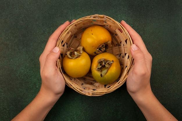 Vista superior de mãos femininas segurando um balde de frutas de caqui em uma superfície verde