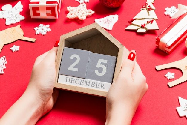 Vista superior de mãos femininas segurando um calendário. o vigésimo quinto de dezembro. decorações de férias. conceito de tempo de natal